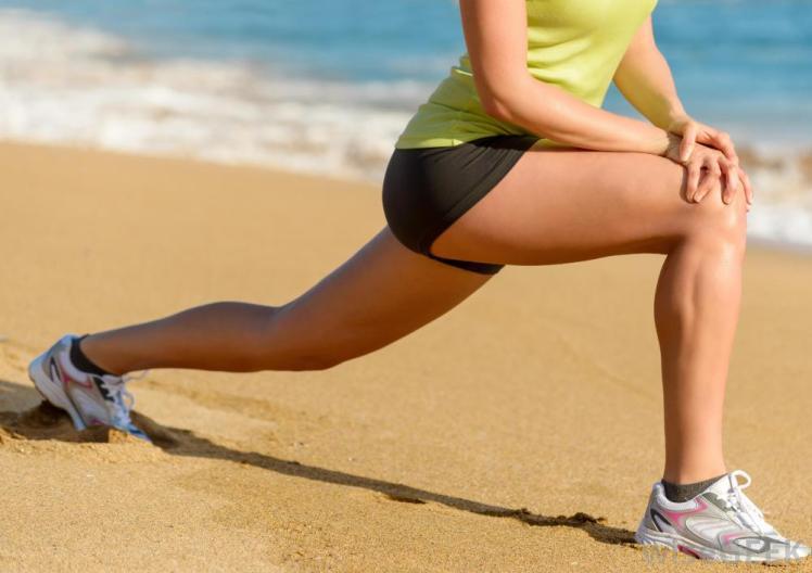 woman-stretching-on-beach-near-water